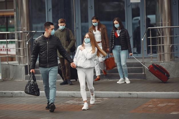 I viaggiatori che lasciano l'aeroporto indossano maschere protettive