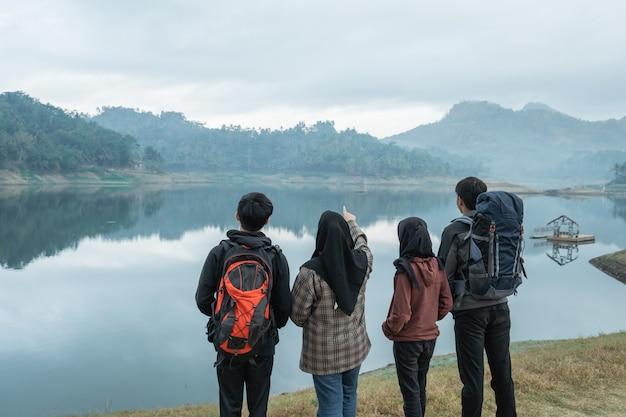 I viaggiatori con zaini che si affacciano godono della vista sul lago dal prato