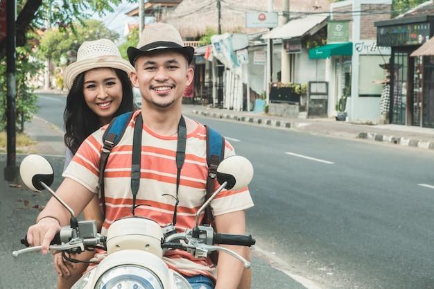 I viaggiatori coppia il sorridere sulla macchina fotografica mentre si siede sulla motocicletta