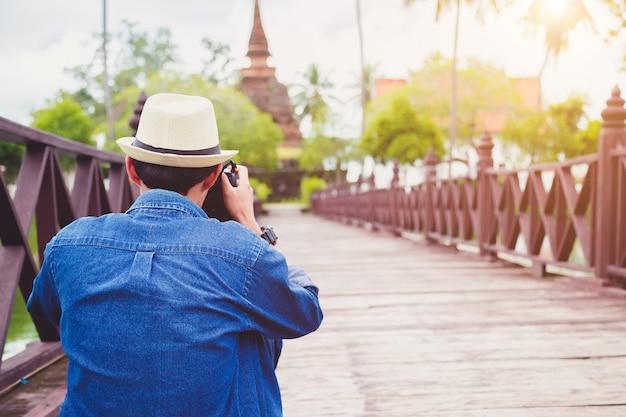 I viaggiatori del giovane stanno godendo delle attrazioni archeologiche. e goditi la fotografia digitale.