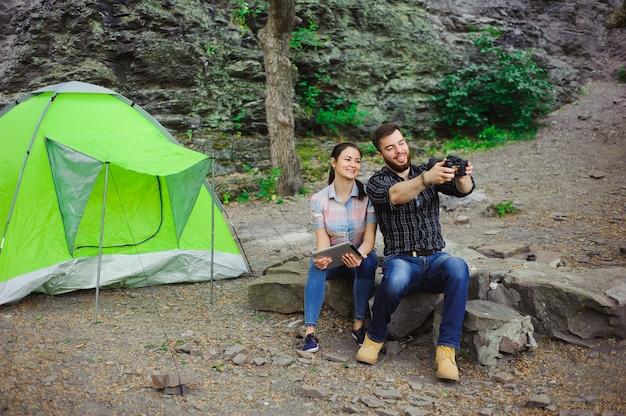 I viaggiatori godono selfie presso la tenda in vacanza estiva in campeggio
