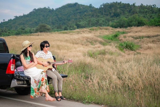 I viaggiatori in coppia hanno un momento di relax durante il viaggio accanto alla strada