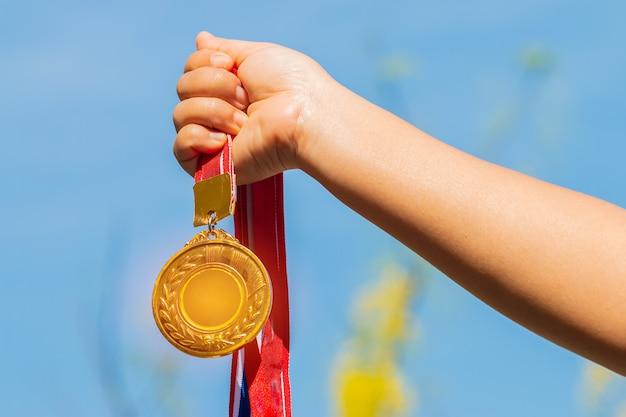 I vincitori o la mano del campione che tiene la medaglia d'oro ricompensa contro il fondo del cielo blu
