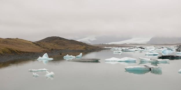 Iceberg galleggianti nell'oceano lungo una costa nebbiosa