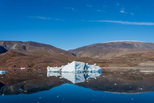 Iceberg nel fiordo della groenlandia con la riflessione in acque calme. tempo soleggiato. ora d'oro.