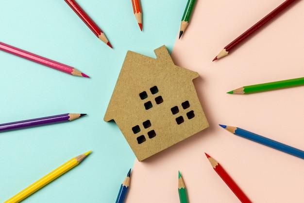 Icona della casa in legno marrone su sfondo blu e rosa