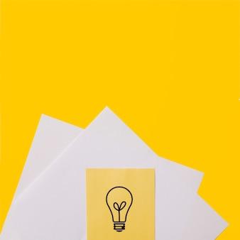 Icona della lampadina di idea sulla nota appiccicosa sopra libro bianco contro fondo giallo
