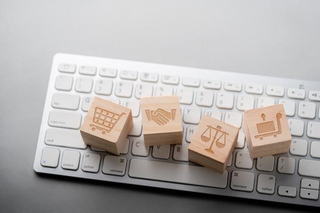 Icona di concetto di strategia commerciale, marketing & shopping online sul cubo e tastiera del computer