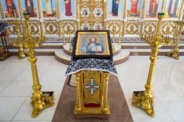 Icona di gesù cristo onnipotente su un supporto dorato accanto a candelabri