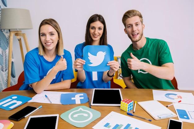 Icona di instagram della holding della donna con i suoi amici che mostrano il segno del thumbup