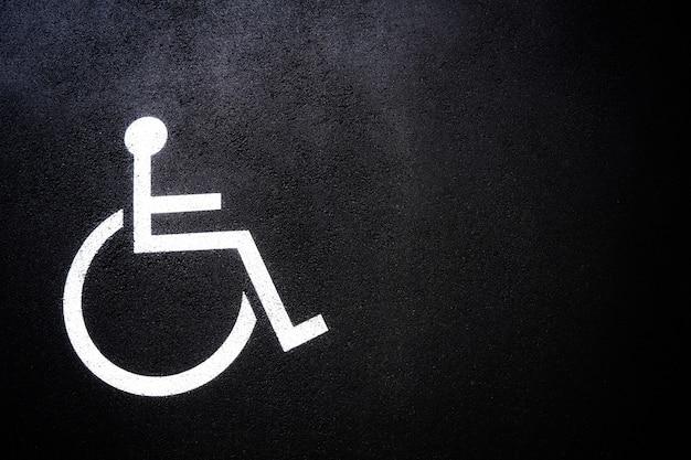 Icona di persone disabili o simbolo di handicap sul parcheggio.