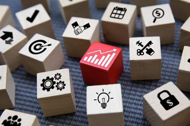 Icone di affari su forma di cubo di legno.