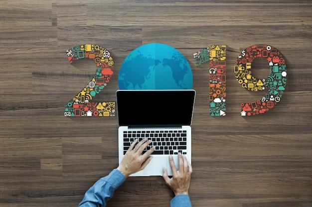 Icone di applicazione di tecnologia di affari del nuovo anno 2019 con lavorare al computer portatile