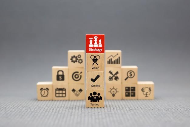 Icone di strategia su blocco di legno per successo, prestazioni, gestione e crescita aziendale.