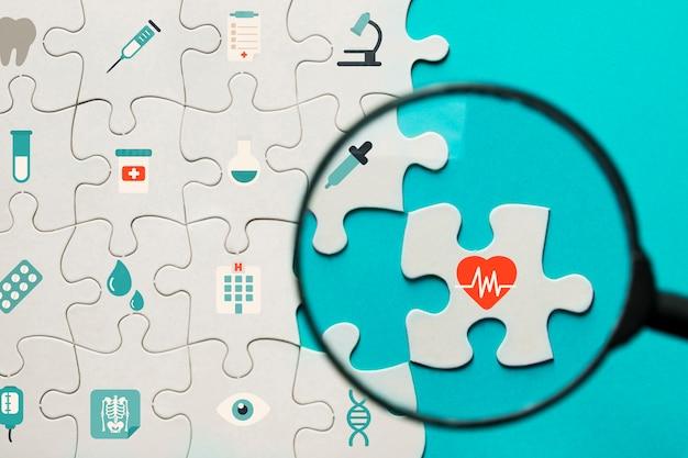 Icone mediche puzzle con lente d'ingrandimento