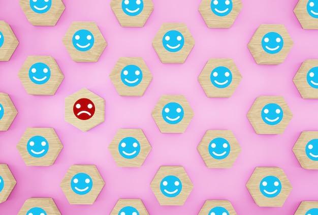 Idea creativa della persona scelta tra gli altri. modello con emoticon faccia felice e triste su esagono di legno