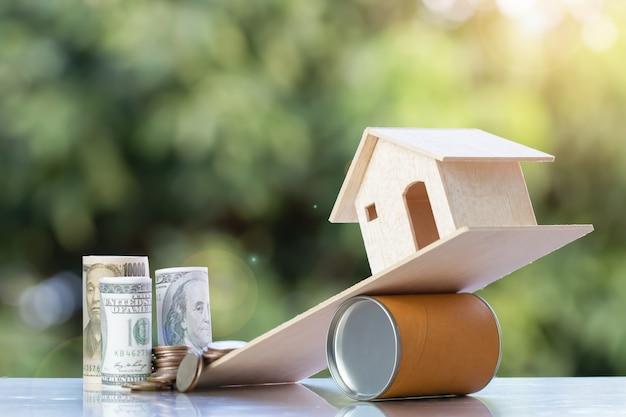 Idea di investimento immobiliare di proprietà: casa in legno su scatola rotonda non bilancia monete dollaro usa jpy