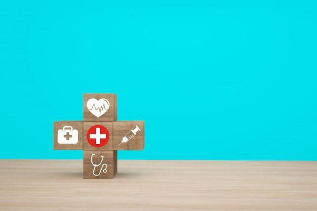 Idea minima di concetto circa dell'assicurazione sanitaria e medica, organizzando l'impilamento del blocco di legno con l'assistenza sanitaria dell'icona medica su fondo blu