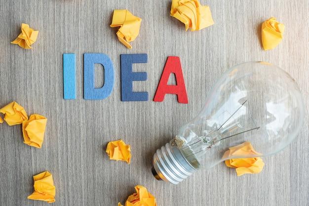 Idea testo e carta sbriciolata con la lampadina sulla tavola di legno
