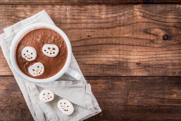 Idea tradizionale per un drink di natale. tazza di cioccolata calda con marshmallow, decorata a forma di pupazzi di neve.