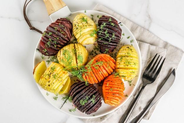 Idee di ricette autunnali di cibo vegano da verdure. patate arrostite delle barbabietole di hasselback con le erbe fresche su un piatto su un fondo di marmo bianco