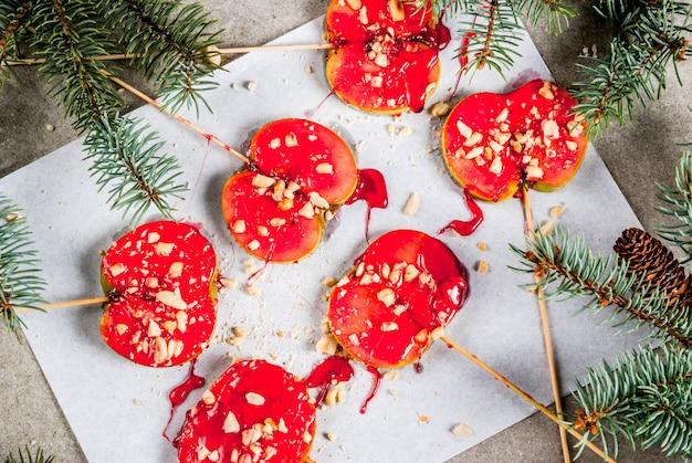 Idee invernali, prelibatezze natalizie. dolci per bambini. fette di mela e cioccolato in caramello e noci rossi. sfondo grigio pietra, con rami di albero di natale, vista dall'alto
