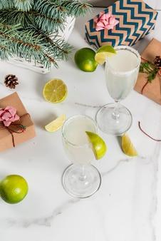 Idee per bevande di natale e capodanno. cocktail margarita champagne, guarniti con lime e sale. sul tavolo bianco con decorazioni natalizie, copia spazio