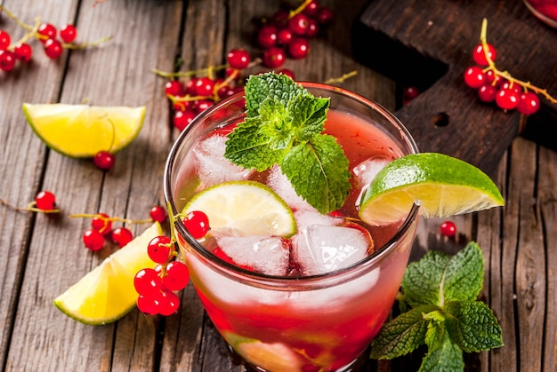 Idee per bevande estive, cocktail dietetici salutari. mojito di lime, menta e ribes rosso. sul vecchio tavolo di legno rustico, con gli ingredienti. copyspace