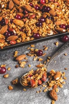 Idee per una colazione autunnale invernale ringraziamento natale granola di miele cotto fresco fatto in casa con noci (mandorle nocciole nocciole) e mirtilli rossi sul tavolo di cemento grigio