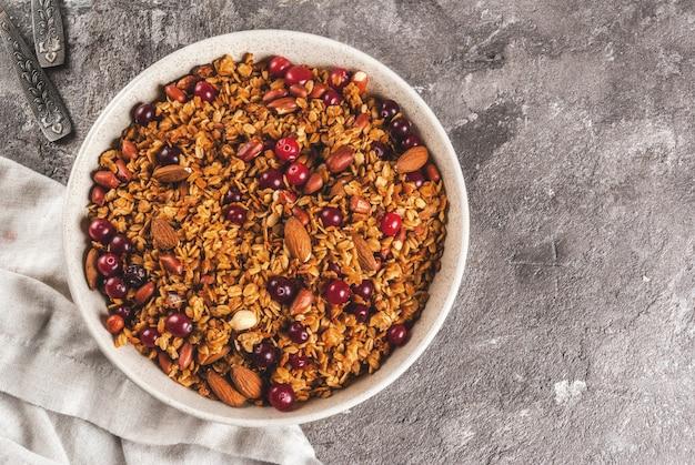 Idee per una colazione invernale, autunnale. ringraziamento, natale. granola di miele cotto fresco fatto in casa con noci (mandorle, arachidi, nocciole) e mirtilli rossi. sul tavolo di cemento grigio, copyspace vista dall'alto