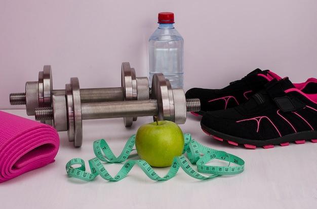 Idoneità femminile. mela verde con manubri, una bottiglia d'acqua, un tappeto, scarpe da corsa e un nastro