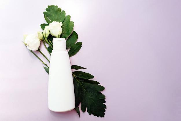 Idratante in un tubo bianco con un foglio naturale sullo sfondo