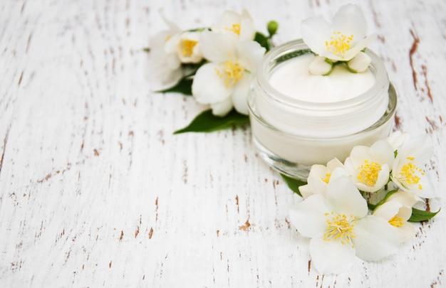 Idratanti crema viso e corpo con fiori di gelsomino su fondo di legno bianco