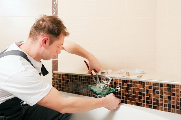 Idraulico che installa un miscelatore in una stanza da bagno