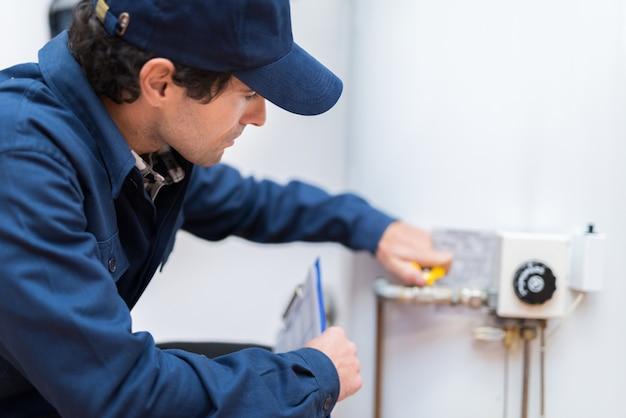 Idraulico che ripara un riscaldatore di acqua calda