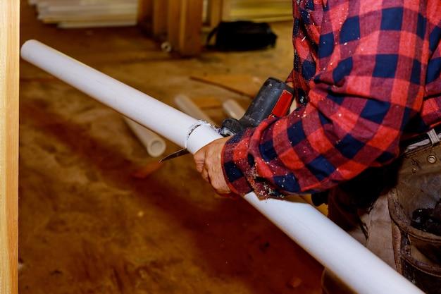 Idraulico che taglia il tubo del pvc nell'uso di un puzzle