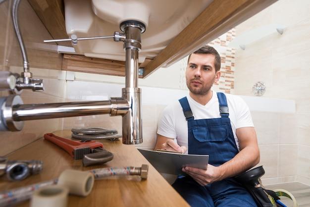 Idraulico con il tablet che ripara il lavandino