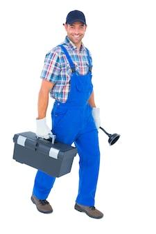 Idraulico felice con il tuffatore e la cassetta portautensili che cammina sul fondo bianco