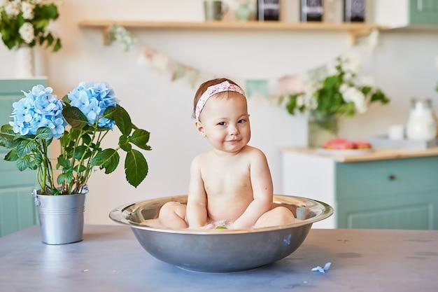 Igiene dei bambini. shampoo, trattamento per capelli e sapone per bambini. fare il bagno bambino in una grande vasca. baby girl wash, igiene infantile, salute e cura della pelle. baby in bath.