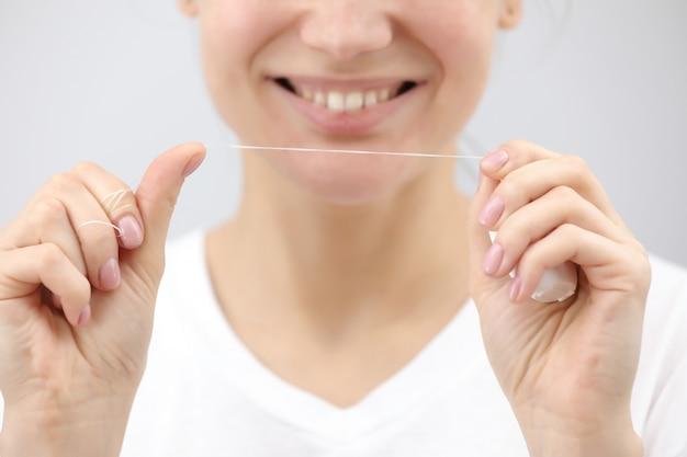 Igiene e cura dentale. filo interdentale. giovane volto di donna in buona salute con il sorriso di bellezza. bella ragazza. persona di assistenza sanitaria.