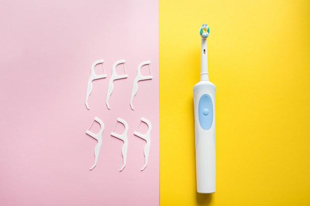 Igiene orale quotidiana per la famiglia. spazzolino da denti elettrico e filo per i denti sulla vista superiore del fondo rosa e giallo, flatlay