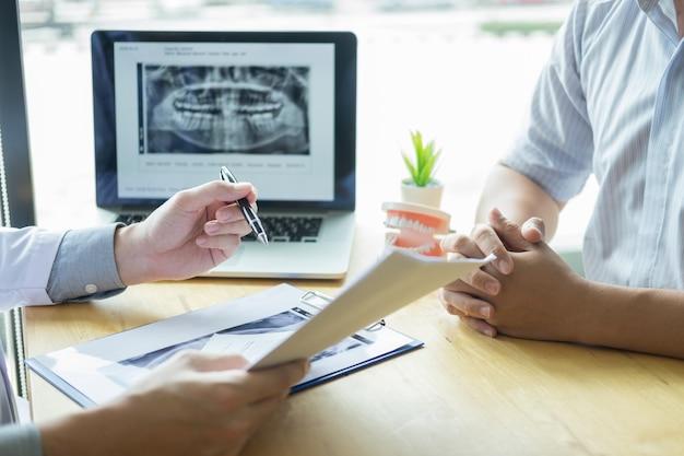 Igienista dentale che mostra e mostra una mascella fittizia per incastrare o guarire i denti del paziente.