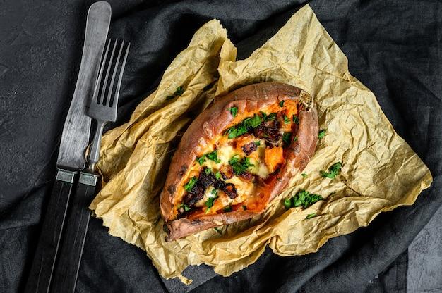 Igname al forno, ripieno di formaggio e pancetta. patata dolce biologica sfondo nero