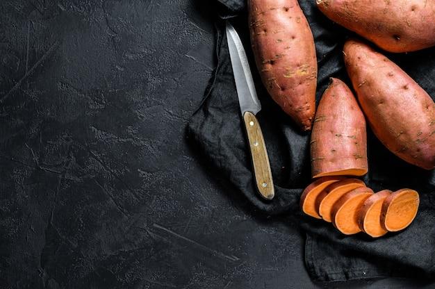 Igname crudo, batate biologiche. il cibo della fattoria. sfondo nero. spazio per il testo
