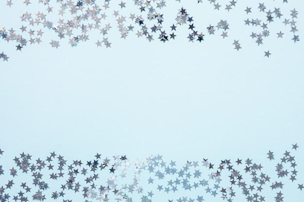 Il backround astratto festivo di natale con i coriandoli della stagnola d'argento stars sull'azzurro