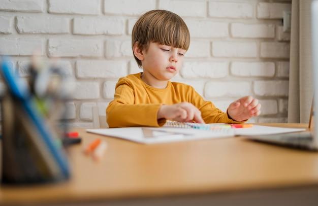 Il bambino alla scrivania viene istruito online