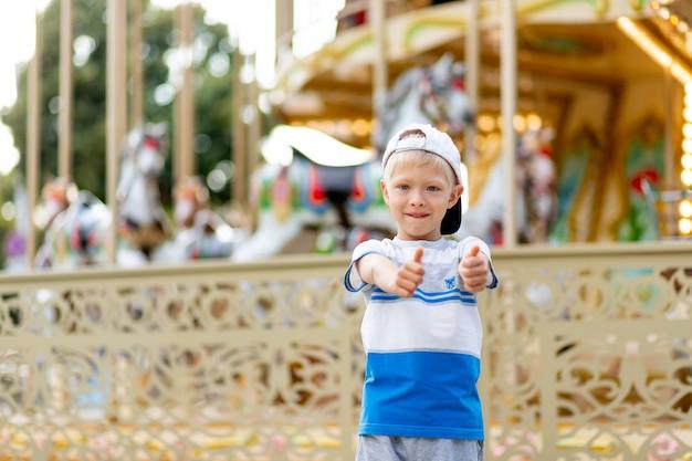 Il bambino allegro cammina in un parco di divertimenti