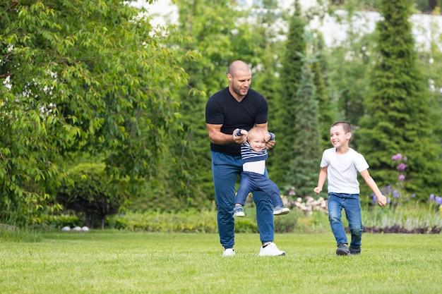 Il bambino allegro sveglio del fratello di due ragazzi con il padre gioca all'aperto nel parco.