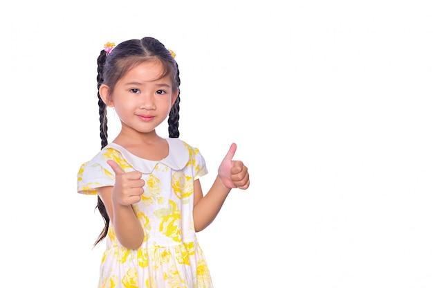 Il bambino asiatico adorabile e allegro che dà i pollici aumenta e sorride il fronte isolato sopra bianco