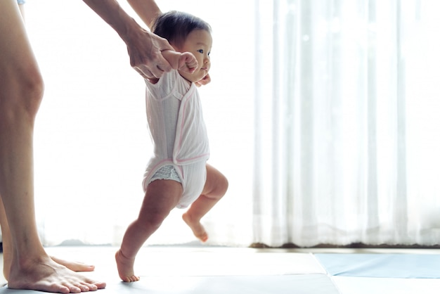 Il bambino asiatico che intraprende i primi punti cammina in avanti sul tappeto morbido